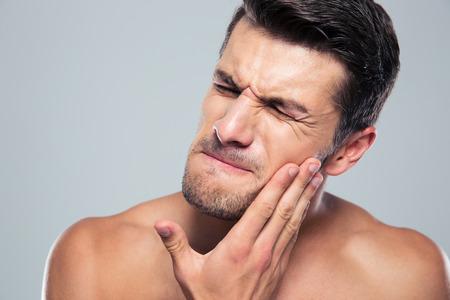 expresiones faciales: Hombre joven con un dolor de muelas m�s de fondo gris Foto de archivo