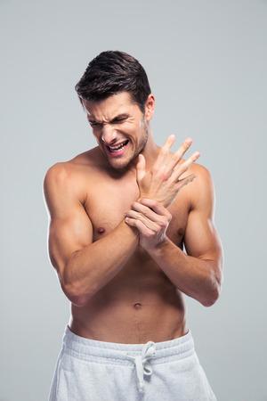 hombre deportista: Hombre que sostiene la mano con dolor en la mu�eca sobre fondo gris