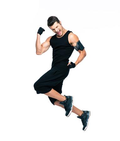 Po celé délce portrét veselý fitness muž skákání na bílém pozadí