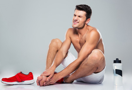 Portrait of a fitness man with foot pain over gray background Stock Photo