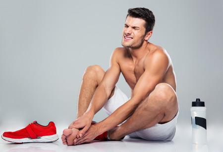 pies masculinos: Retrato de un hombre de fitness con dolor de pie sobre fondo gris