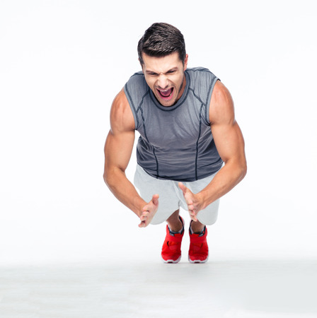 Fitness handsome man doing push ups and shouting isolated on a white background