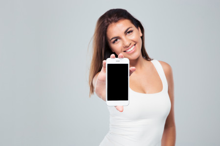 Smiling woman showing smartphone screen over gray background. Looking at camera. Focus on smartphone