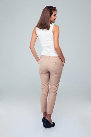 cuerpo completo: Volver la vista vertical de una mujer casual de pie sobre fondo gris