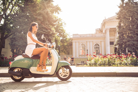 vintage dress: Young happy woman driving vintage scooter in old european town Stock Photo