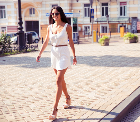 classy woman: Full length portrait of a happy fashion woman walking in town