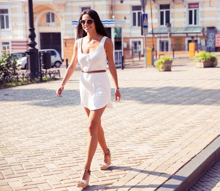 cuerpo completo: Retrato de cuerpo entero de una mujer de moda feliz caminando en la ciudad