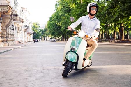 旧市街のヘルメットでスクーターを運転ファッション男 写真素材