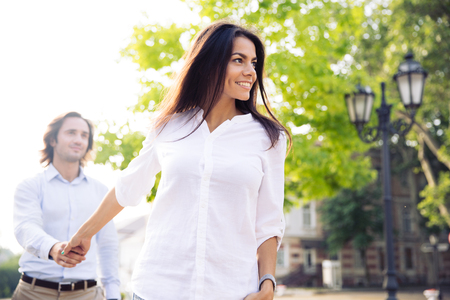 Happy woman holding man's hand and leading him outdoors Stock Photo - 130059280