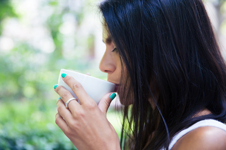green day: Side view portrait of a woman drinking coffee outdoors
