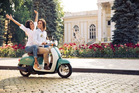 Happy young couple traveling in scooter in old european city Foto de archivo