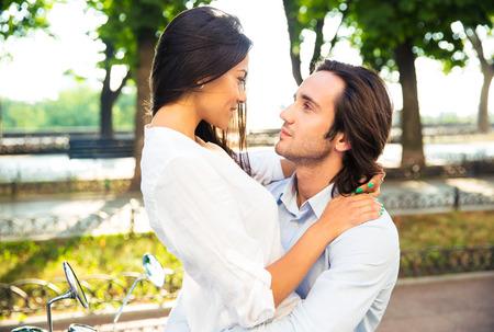 pareja abrazada: Joven pareja feliz abrazando al aire libre y mirando el uno al otro