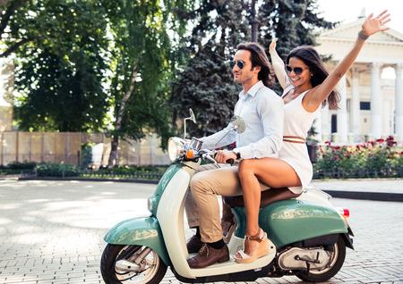 古いヨーロッパの町でスクーターに乗って幸せなカップル
