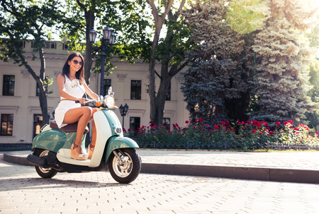 Cheerful young woman driving scooter in town