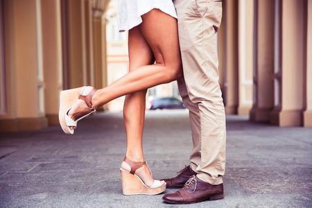 bacio: Ritratto del primo piano di un maschio e femmina gambe durante una data