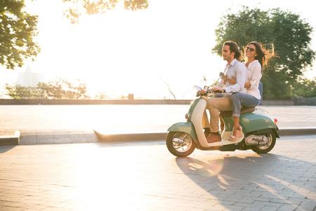 スクーターに乗っていて、楽しい幸せな若いカップル。朝の太陽が輝いています。
