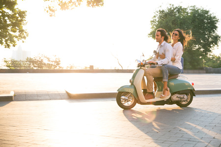 fun: Happy young couple riding a scooter and having fun. Sun is shining in the morning Stock Photo