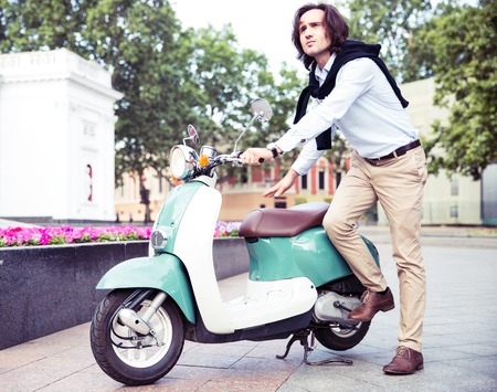cool people: Man starts his scooter in old european town