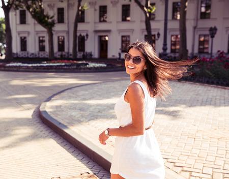 サングラスと野外を歩いているドレスで幸せな女は。カメラを目線