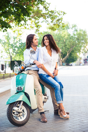 each: Happy young couple on scooter looking at each other outdoors