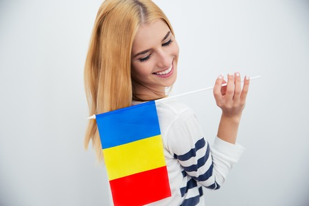 rumania: Happy young woman holding Romanian flag over gray background