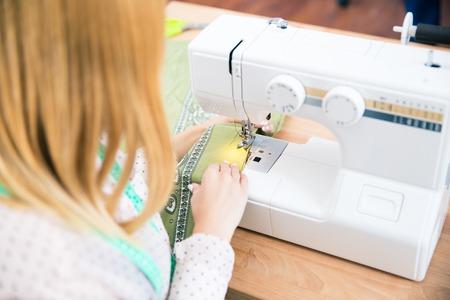 Closeup portrait of female tailor using a sewing machine