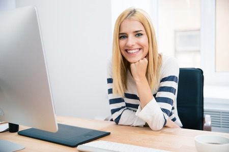 artist: Cheerful young female designer sitting at the table in office and looking at camera