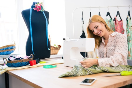 alterations: Pretty young woman using sewing machine in laundry Stock Photo