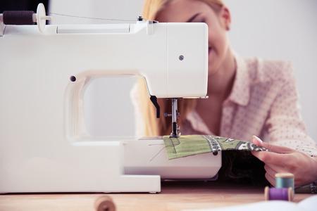 Closeup portrait of female tailor using sewing machine in workshop. Focus on machine