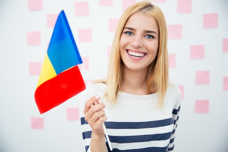 rumania: Happy woman holding Romanian flag over gray background and looking at camera