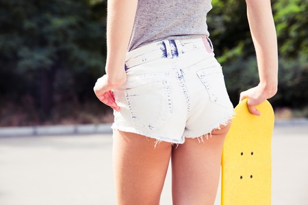 female ass: Back view portrait of a young female ass in shorts with skateboard outdoors Stock Photo