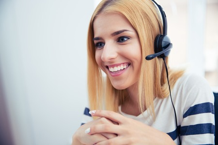 customer service: Happy young female operator in headphones working at office