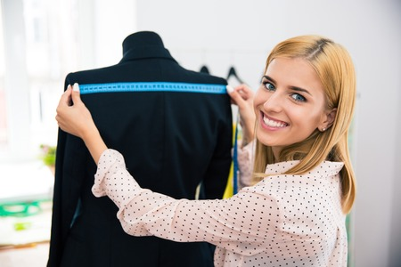 tailor measuring tape: Smiling female tailor measuring tape jacket on mannequin and looking at camera Stock Photo