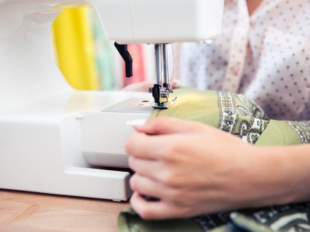 alterations: Closeup portrait of a woman using a sewing machine
