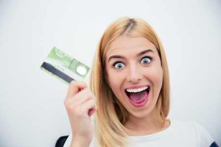 happy shopper: Cheerful young woman holding bank card over gray background Stock Photo