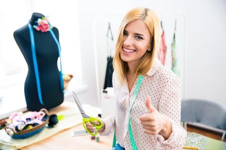 笑顔の女性テーラー ワーク ショップに立って、親指を表示