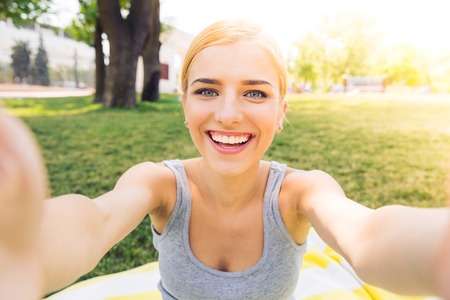 rubia: Retrato de una chica joven sonriente que hace la foto selfie en el parque Foto de archivo