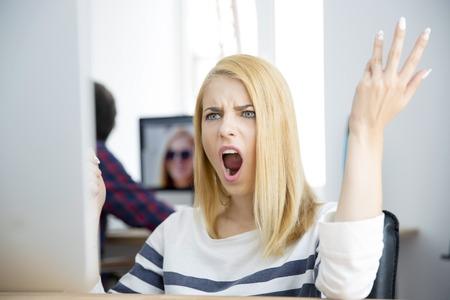 Geschokt jonge vrouw die op de computer in kantoor Stockfoto