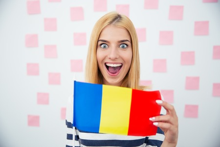 rumania: Cheerful young woman holding Romanian flag with stickers on background. Looking at camera
