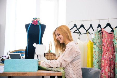 alterations: Happy beautiful woman using sewing machine in laundry Stock Photo