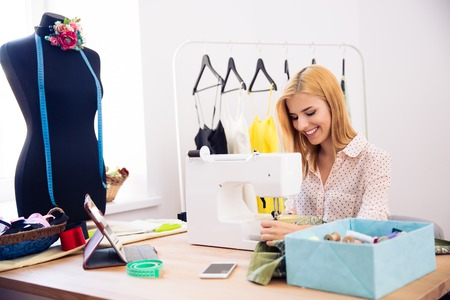 alterations: Happy young woman using a sewing machine in laundry Stock Photo