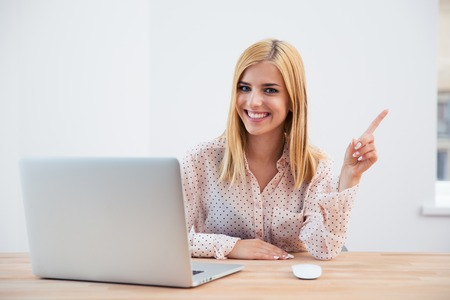 looking away from camera: Smiling businesswoman sitting at the table with laptop and poing finger away over gray background. Looking at camera