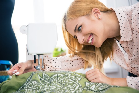alterations: Happy female designer working on sewing machine