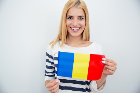 rumania: Smiling young girl holding Romanian flag over gray background. Looking at camera