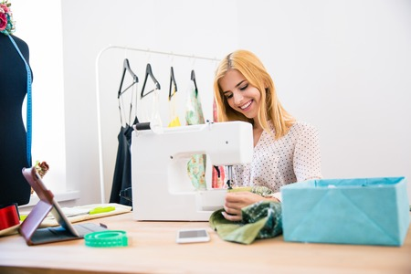 alterations: Happy female tailor using sewing machine in laundry