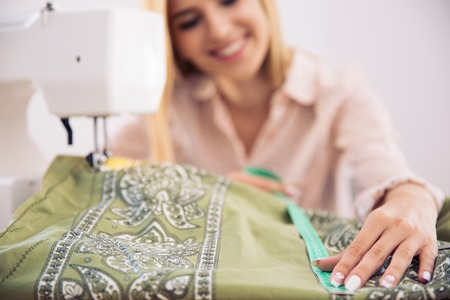Haooy female tailor working in workshop. Focus on cloth Stock Photo