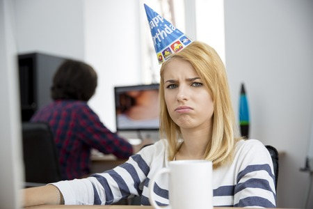attired: Sad woman with birthday hat sitting at the table in office and looking at camera Stock Photo