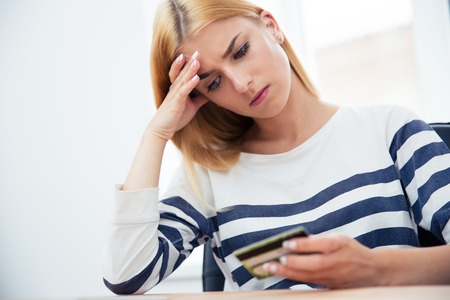 credit card bills: Unhappy casual woman holding bank card