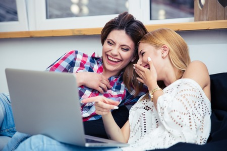 Two laughing girls sitting on sofa and watching movie on laptop