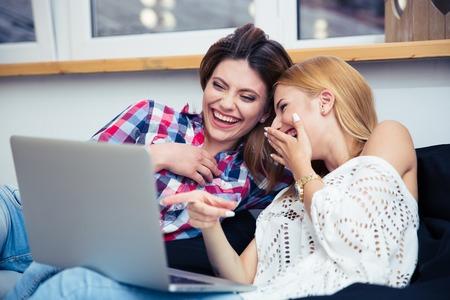 mujer viendo television: Dos muchachas de risa sentado en el sofá y viendo la película en la computadora portátil